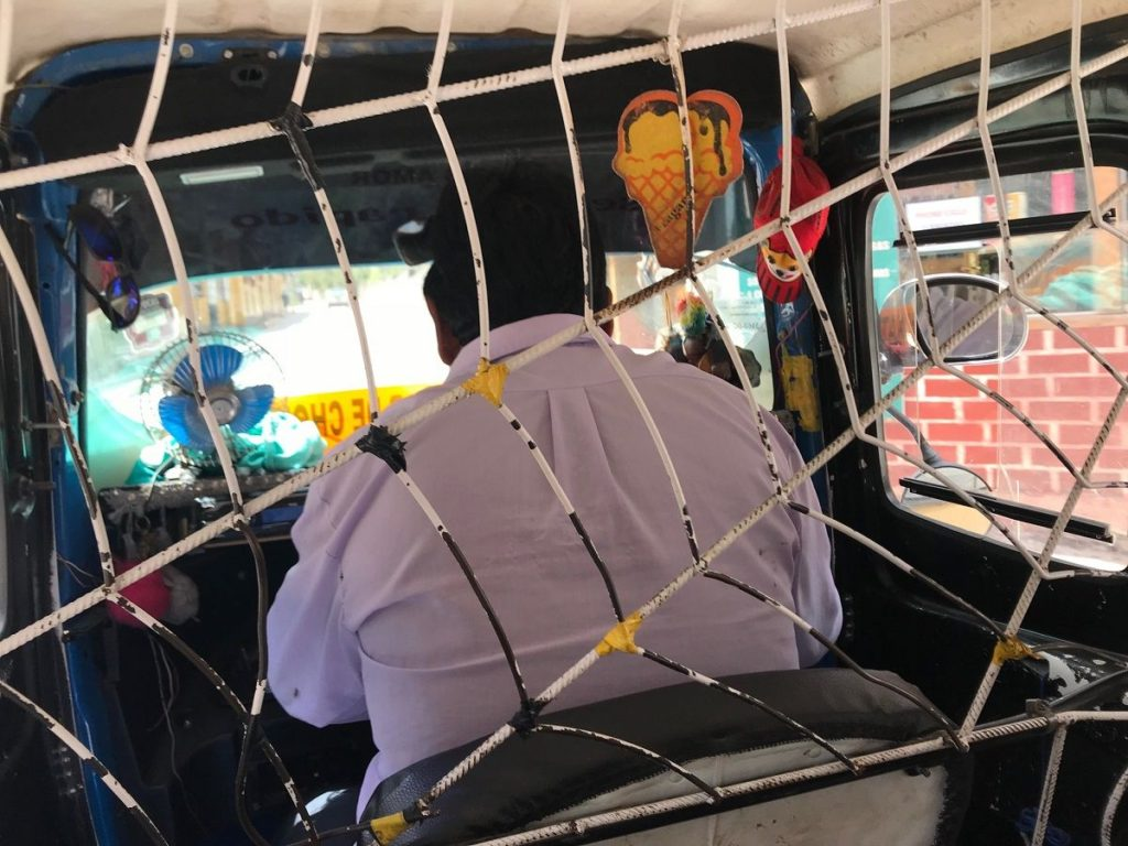 トゥクトゥクみたいな乗り物の後部座席から、おじちゃんの背中